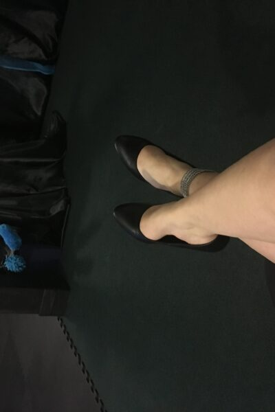 Photo of Scarlet Darlings legs outstretched and crossed at the ankles, in black heels. NZ Pleasures.