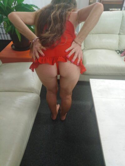 Angeliquea bending over in front of the camera, buttocks to camera, hands on tops of buttocks. Angeliquea wears a red teddy and has long light brown hair. NZ Pleasures.