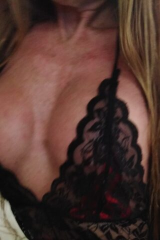 Close up photo of Angeliquea's chest in a black lace chemise, her long brown hair falling down either side of breasts. NZ Pleasures.
