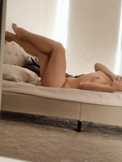 Sienna lying on her back on a bed, feet up on top of headboard, one arm across one breast. Sienna is naked. NZ Pleasures.