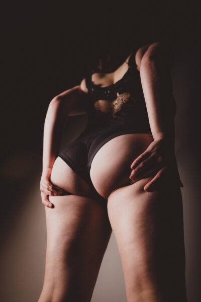 Lilah standing with back to camera, legs wide apart, hands cupping the bottom of each buttock. Lilah wears a black bodysuit and has long brown hair. NZ Pleasures.
