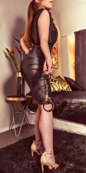 Ivy Grace posing side on to camera, hand cuffs in one hand, her other hand on hip. Ivy wears a tight black sleeveless dress, beige heels and her long auburn hair in a ponytail. NZ Pleasures.