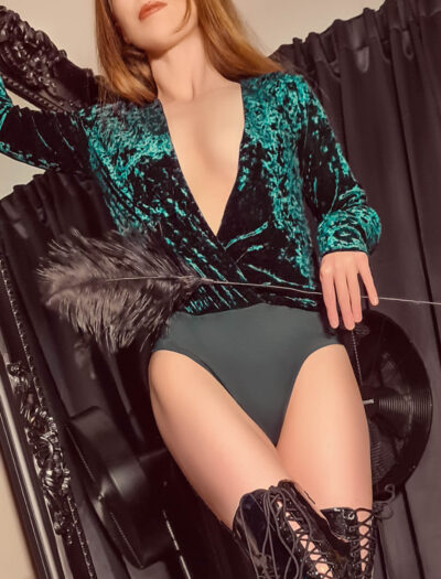 Ivy Grace posing with a feather in one hand, one leg in front of the other, her other hand resting on the side of the mirror she stands beside. Ivy wears a emerald green bodysuit with a velvet upper, black over the knee boots and has long auburn hair. NZ Pleasures.