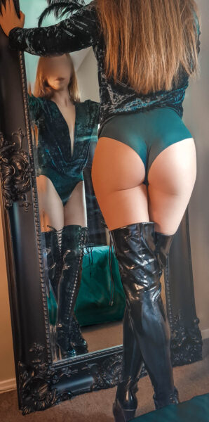 Ivy Grace standing in front of a mirror, one leg in front of the other, hands up on either side of mirror, back to camera. Ivy wears a emerald green bodysuit with a velvet upper, black over the knee boots and has long auburn hair. NZ Pleasures.