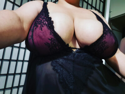 Dita Lovegood from shoulders to stomach, wearing a black and maroon teddy, taking a selfie from out front. NZ Pleasures.
