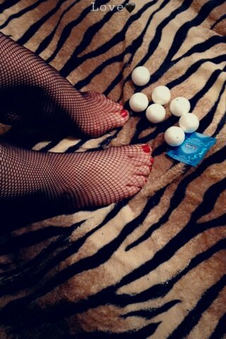Fleur's feet on a tiger print blanket next to condoms, Fleur wears black fishnet stockings and her toenails are painted red. NZ Pleasures.