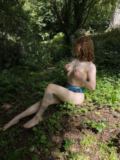 Ivy Sinclair sitting in the bush, one leg extended in front of her, the other bent up, hands on on breasts. Ivy wears blue panties and has shoulder length auburn hair. NZ Pleasures.