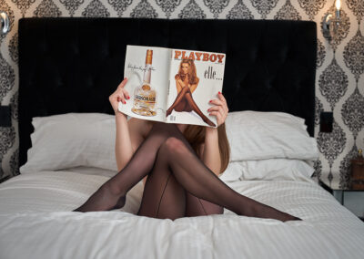 Zara Marlow sitting on a bed, legs crossed, feet resting on the bed, holding a Playboy magazine infront of her face. Zara wears black stockings and has long brown hair. NZ Pleasures.
