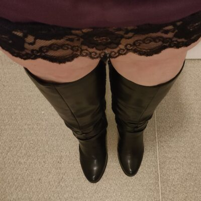 Corrine from thighs down in a black mini skirt and black over the knee boots. NZ Pleasures.