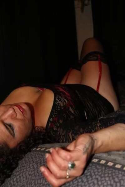 Rita lying on her back, knees bent up, hand by side of head. Rita wears black lingerie with suspender belt and thigh high stockings. NZ Pleasures.