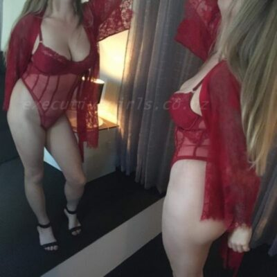 Alice standing in front of a mirror, one knee bent forward, one arm behind buttock, other hand up on mirror above head. Alice wears a red bodysuit, red lace kimono that is undone, black heels and has long blonde hair. NZ Pleasures.