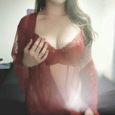Alice posing with one hand on breast. Alice wears red lingerie and a red lace kimono that is undone and off one shoulder. Alice has long blonde hair. NZ Pleasures.