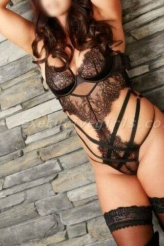 Alora standing with back against the wall, one knee bent up, foot on the wall, arms above head. Alora wears a black lace bodysuit, black thigh high stockings and has long dark brown hair. NZ Pleasures.
