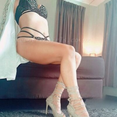 Amber sitting on the edge of a bed, one foot in front of the other, leaning back on hands behind her. Amber wears black and gold lingerie, a white kimono that is undone and beige strappy heels. NZ Pleasures.