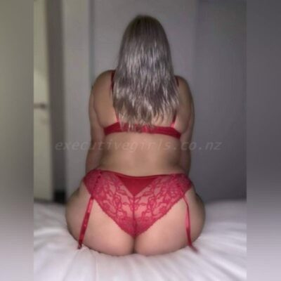 Bella sitting on the edge of a bed, back to camera, hands on tops of thighs. Bella wears red lingerie and has long blonde hair. NZ Pleasures.