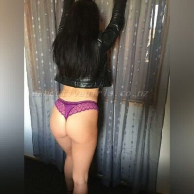 Carla standing with back to camera, arms on wall in front of her, one knee bent forward. Carla wears a black leather jacket, purple panties, beige heels and has long dark brown hair. NZ Pleasures.