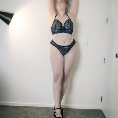 Celeste standing with one leg in front of the other, arms above head. Celeste wears black lingerie and black heels. NZ Pleasures.