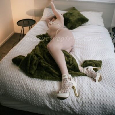 Celeste lying on her side on a bed, arms above head, one leg crossed over the other, a dark green rug draped between legs. Celeste wears white lingerie with white lace boot stilettos and has dark brown shoulder length hair. NZ Pleasures.