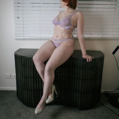 Celeste sitting on a cabinet, one leg tucked behind the other, leaning on one hand out to one side, the other hand behind her, head turned over shoulder away from camera. Celeste wears lilac lingerie and gold heels and has dark brown shoulder length hair. NZ Pleasures.
