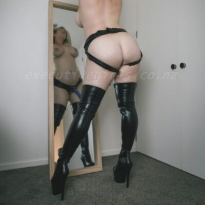 Delphie stand with legs wide apart, back to camera, arms above head, a mirror in front of her shows her reflection. Delphie wears a black strapon and black thigh high stiletto boots and has shoulder length multi-coloured hair. NZ Pleasures.