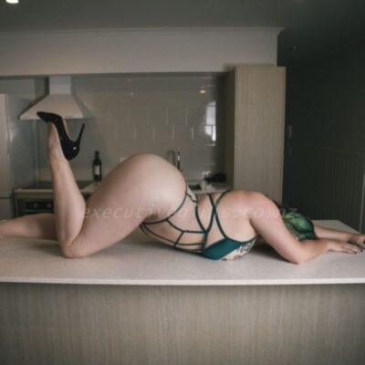 Delphie lying on her front on a kitchen bench, one knee bent, foot in air, arms out in front of her. Delphie wears a dark green and light beige bodysuit and black stilettos and has multi-coloured shoulder length hair. NZ Pleasures.