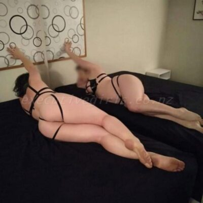 Delphi lying on her side on a bed, back to camera, one knee bent up slightly along other leg, one arm up on wall behind her. Her reflection in the mirror along side the bed. Delphi wears black lingerie and has multi-coloured shoulder length hair. NZ Pleasures.