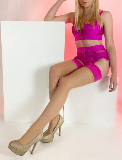 Lucca perching on the top of a white plinth, knees bent, one foot extended further out than the other, one arm by side, the other resting on top of another plinth, hand on head. Lucca wears magenta lingerie with stockings and gold stilettos and has long blonde hair. NZ Pleasures.