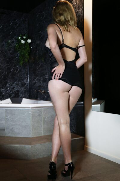 Saama posing with back to camera, one leg crossed over the other, one hand on side of buttock, the other at waist height. Saama wears a black mini dress that is pulled half way up her buttocks, black heels and has long blonde hair. NZ Pleasures.