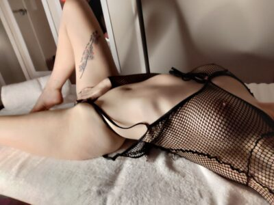 Rosa Rylie lying on her back on a towel on a massage table, one leg bent up, opposite arm above head, her other hand rests over vulva. Rosa wears a black fishnet stocking top and black thong. NZ Pleasures.