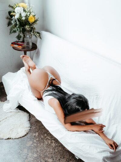 Alma Rue on knees and elbows on a couch, arms out in front of her, head down, feet in air. Alma wears a white singlet, white g-string and has long black hair. NZ Pleasures.