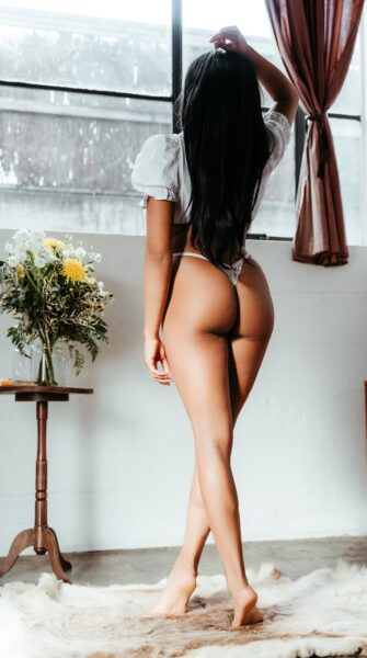 Alma Rue standing on tip toes, back to camera, one leg in front of the other, one arm by side, the other on top of head. Alma wears a white top, white panties and has long black hair. NZ Pleasures.