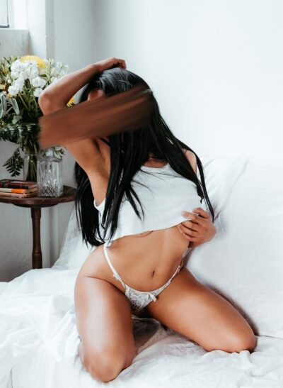 Alma Rue kneeling on a bed, siting back on heels, knees apart, one arm over head, the other hand on breast. Alma wears a white singlet that is pulled up just below breasts, white panties and has long black hair. NZ Pleasures.