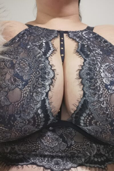 Close up photo of Dita Lovegood's breasts in a blue and silver bra, a grey fur boa draped over her arms. NZ Pleasures.