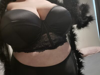Dita Lovegood from chest to hips, wearing black lingerie and a black sheer kimono with feather detail that is undone. NZ Pleasures.