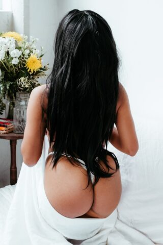 Alma Rue kneeling with back to camera, holding a white sheet around base of buttocks. Alma wears white g-string and has long black hair. NZ Pleasures.