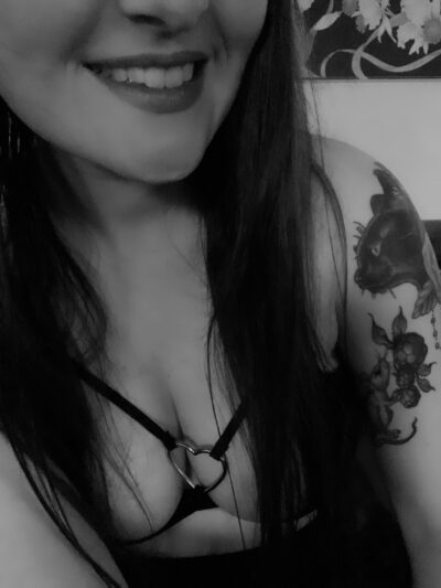 Black and white photo of Gemma Rose from nose to chest. Gemma wears a black bra with a metal love heart in the middle, her long hair down either side of breasts. NZ Pleasures.