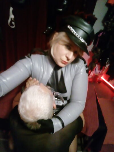 Mistress Ilka taking a selfie while holding a sub to her chest. Mistress Ilka wears a black and grey pvc jacket, black cap with chain detail. NZ Pleasures.