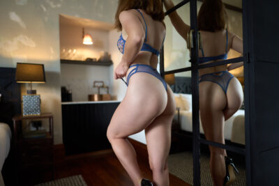 Zara Marlow standing beside a mirror, partially side on to camera, back and buttocks reflected in mirror. Zara stands with one knee bent forward, one hand pulling on the side of her panties. Zara wears blue lingerie and has auburn hair. NZ Pleasures.