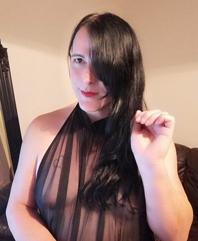 Portrait style photo of Amy Maxine posing with hand by side of face, her long black hair down one side of face. Amy wears a black sheer top. NZ Pleasures.
