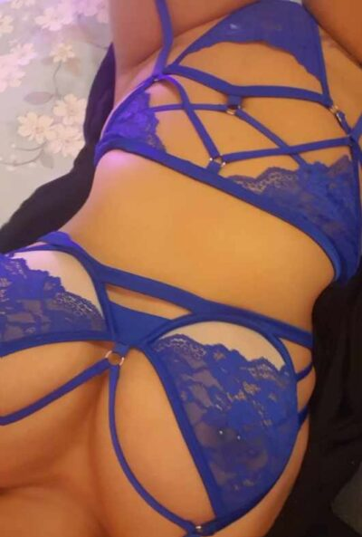 Jasmine lying on her back, knees bent up. Photo cropped from chest to upper thighs. Jasmine wears blue lingerie. NZ Pleasures.