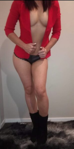Mia posing with one knee bent forward, leaning forward slightly, hands pulling on sides of the red jacket she wears that is undone. Mia wears black panties and has long dark brown hair. NZ Pleasures.