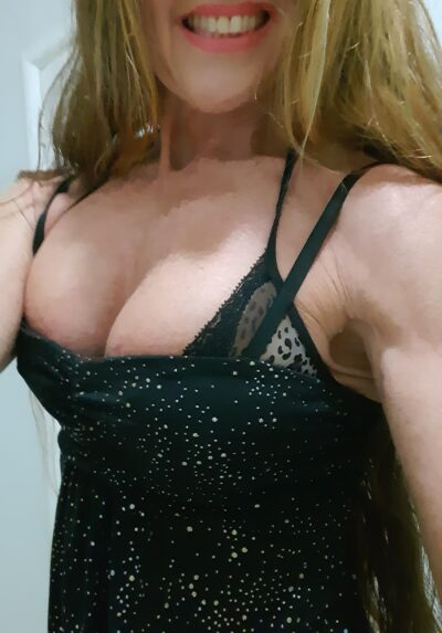 Angeliquea taking a selfie from lips to hips, smiling at camera. Angeliquea wears a black shoestring strap dress with silver diamantes and has long blonde hair. NZ Pleasures.