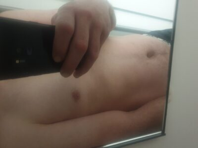 Roman taking a selfie of his chest and stomach in a mirror. NZ Pleasures.