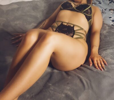 Peach lying on her back with knees bent, ankles crossed, hands either side of hips. Peach wears black and gold lingerie. NZ Pleasures.