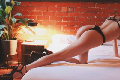 Rosa Rylie kneeling on one knee and on both hands across a bed, side on to camera, her other leg extended out behind her. Rosa wears black lingerie and black wedge stilettos. NZ Pleasures.