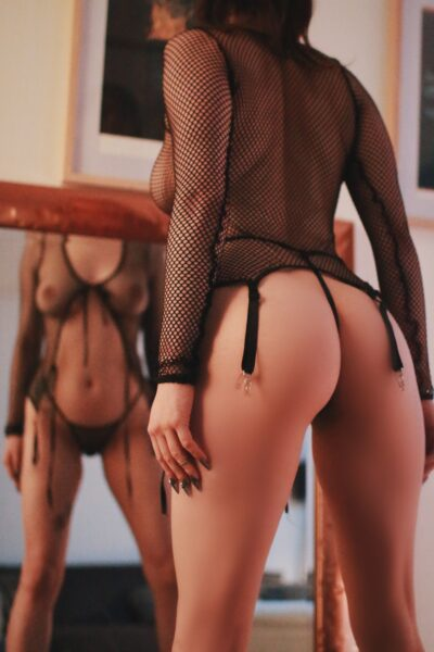 Rosa Rylie posing with back to camera, standing with legs wide apart, hands by sides in front of mirror, you can see her reflection. Rosa wears a black fishnet stocking top that ties under the breasts and black panties. NZ Pleasures.