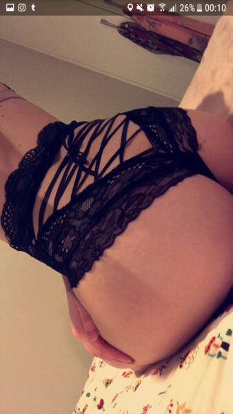 Tilly Watts taking a selfie while kneeling on a bed, sitting back on feet, back to camera, one hand resting on side of thigh. Tilly wears black lingerie. NZ Pleasures.