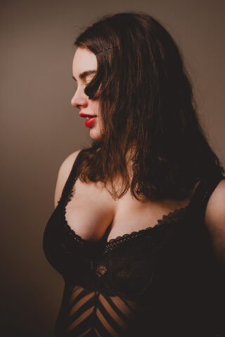 Portrait style photo of Lilith posing with hands behind back, head titled down, a lock of hair falling over her face. Lilith wears black bodysuit and has long dark brown hair. NZ Pleasures.
