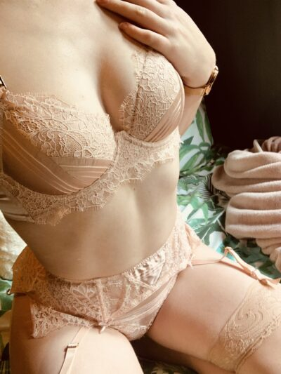 Tilly Watts kneeling, sitting back on feet, legs apart, one hand on top of chest. Tilly wears beige lingerie with suspender belt and beige thigh high stockings. NZ Pleasures.