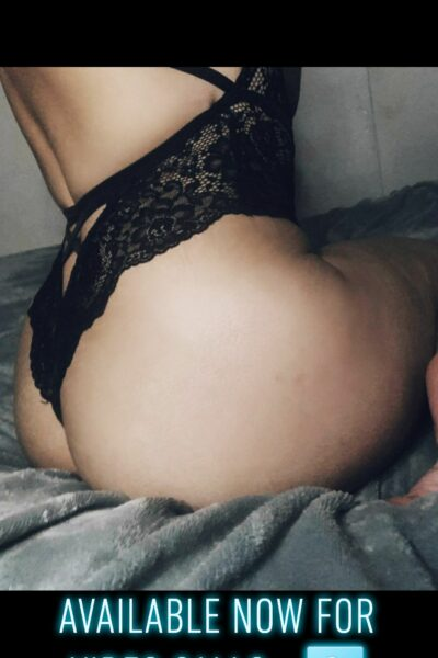 """Peach sitting side on to camera, arms above head, wearing a black lace bodysuit. The text """"Available now for video calls"""" is on the bottom of the photo. NZ Pleasures."""